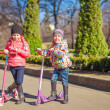Two lovely sisters ride scooters on a warm sunny spring day — Stock Photo #43862241