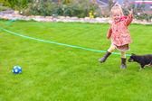 Menina bonitinha brincando com seu cachorro no quintal — Foto Stock