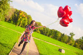 Young happy girl have fun with red balloons outside — Stock Photo