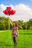 Young happy girl have fun with red balloons outdoor — Zdjęcie stockowe