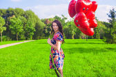 Young happy woman with red balloons walking in the park — Stockfoto