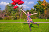 Young happy girl in colorful dress have fun with red balloons outside — Stock Photo