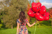 Back view of young woman with red smiling balloons in hand — Stock Photo