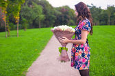 Beautiful large bouquet white roses at the hands of a young girl in colored dress — Stock Photo