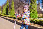 Portrait of beautiful toddler girl on the scooter in warm spring day — Stock Photo
