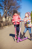 Little happy girls with scooter in spring park at warm day — Stock Photo