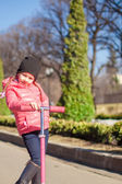 Adorable little girl have fun on the scooter in warm spring day — Stock Photo