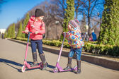 Little beautiful girls with scooter in spring park — Stock Photo