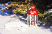 Beautiful red fairytale lantern on white snow in forest — Stock Photo