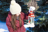 Young beautiful happy woman with red Christmas lantern in the snow — Stock Photo