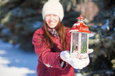 Young beautiful happy woman with red Christmas lantern in the snow — Photo