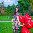 Closeup of young beautiful woman in colorful dress with red balloons — Stock Photo