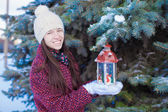 Young beautiful girl with red Christmas lantern in the snow — ストック写真