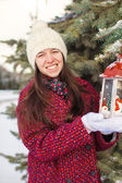 Young beautiful woman with red Christmas lantern in the snow — Stock Photo