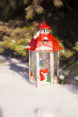 Beautiful red fairytale lantern on white snow near Christmas tree — Stok fotoğraf