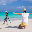 Little adorable girl making photo of her young father at exotic beach — Stock Photo #45405977