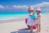 Little lovely girls with big suitcase and a map on tropical beach — Stock Photo