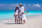 Family of four on caribbean beach summer vacation — Stock Photo