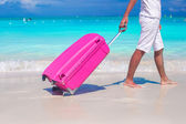 Close up a man pulls luggage on white sand — Stock Photo