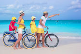 Young family riding bicycles on a tropical beach — Stock Photo