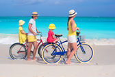 Young family of four riding bicycles on a tropical sand beach — Stock Photo