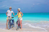 Young happy couple riding bikes on white tropical beach — ストック写真