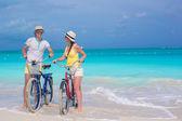 Young happy couple riding bikes on white tropical beach — Stock Photo