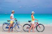 Young happy couple riding bikes on white sandy beach — Stock Photo