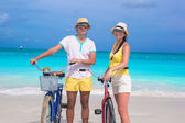 Young happy couple with bikes on white sandy beach — Stock Photo