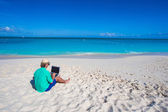 Young man with laptop on background of turquoise ocean — Stock Photo