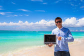 Young man with laptop on the background of turquoise ocean at tropical beach — Stock Photo