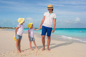 Adorable little girls and happy father on tropical white beach — Stock Photo