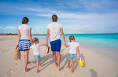 Back view of a young beautiful family on tropical beach — Stock Photo