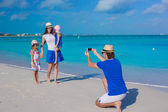 Young father making photo on phone of his family at the beach — Stock Photo