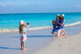 Little girl making photo on phone of her family at the beach — Stock Photo