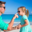 Father apply sunblock cream on his little child nose — Stock Photo