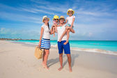 Happy family of four on beach tropical vacation — Stock Photo