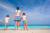 Young happy mother and her adorable daughters having fun at exotic beach on sunny day — Stock Photo