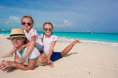 Happy father and his adorable little daughters at tropical beach — Stock Photo