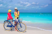 Happy mother and her daughter riding bicycles on a tropical beach — Stock Photo