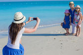 Young mother making photo on phone of her family at the beach — Stock Photo