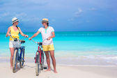 Young happy couple with bikes on summer beach vacation — 图库照片