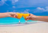 Two hands hold glasses with orange juice background blue sky — Stock Photo