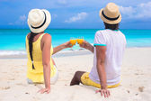 Happy couple with two glasses of orange juice on beach vacation — Stock Photo