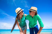Happy young couple on exotic beach looking at camera — Stock Photo