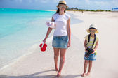 Little girl with camera and young mother walking at beach — Stock Photo