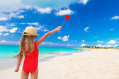 Little girl with red heart in hands on a tropical beach — Foto de Stock