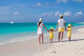 Back view young family of four on tropical beach — Stockfoto