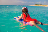 Little adorable girl on a surfboard in the turquoise sea — 图库照片