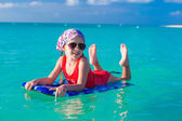 Little girl swimming on a surfboard in the turquoise sea — Foto de Stock